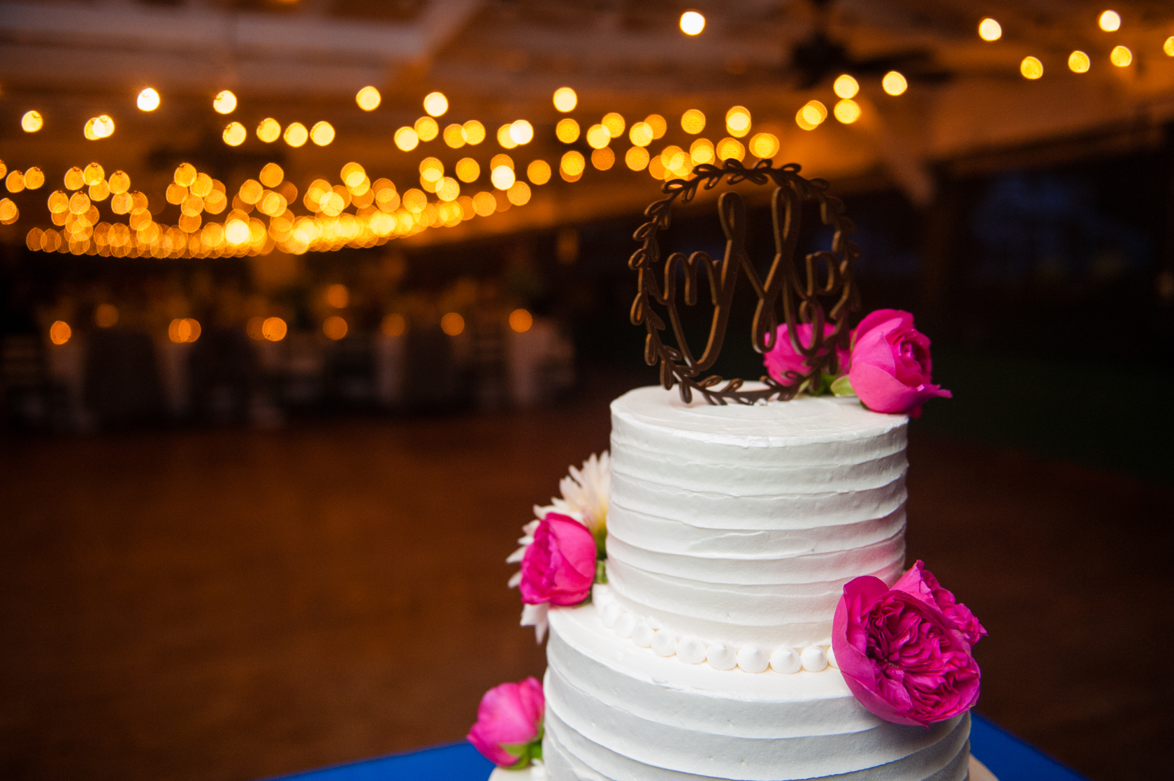 elegant wedding cake with real flowers was a beautiful addition to this summer camp wedding