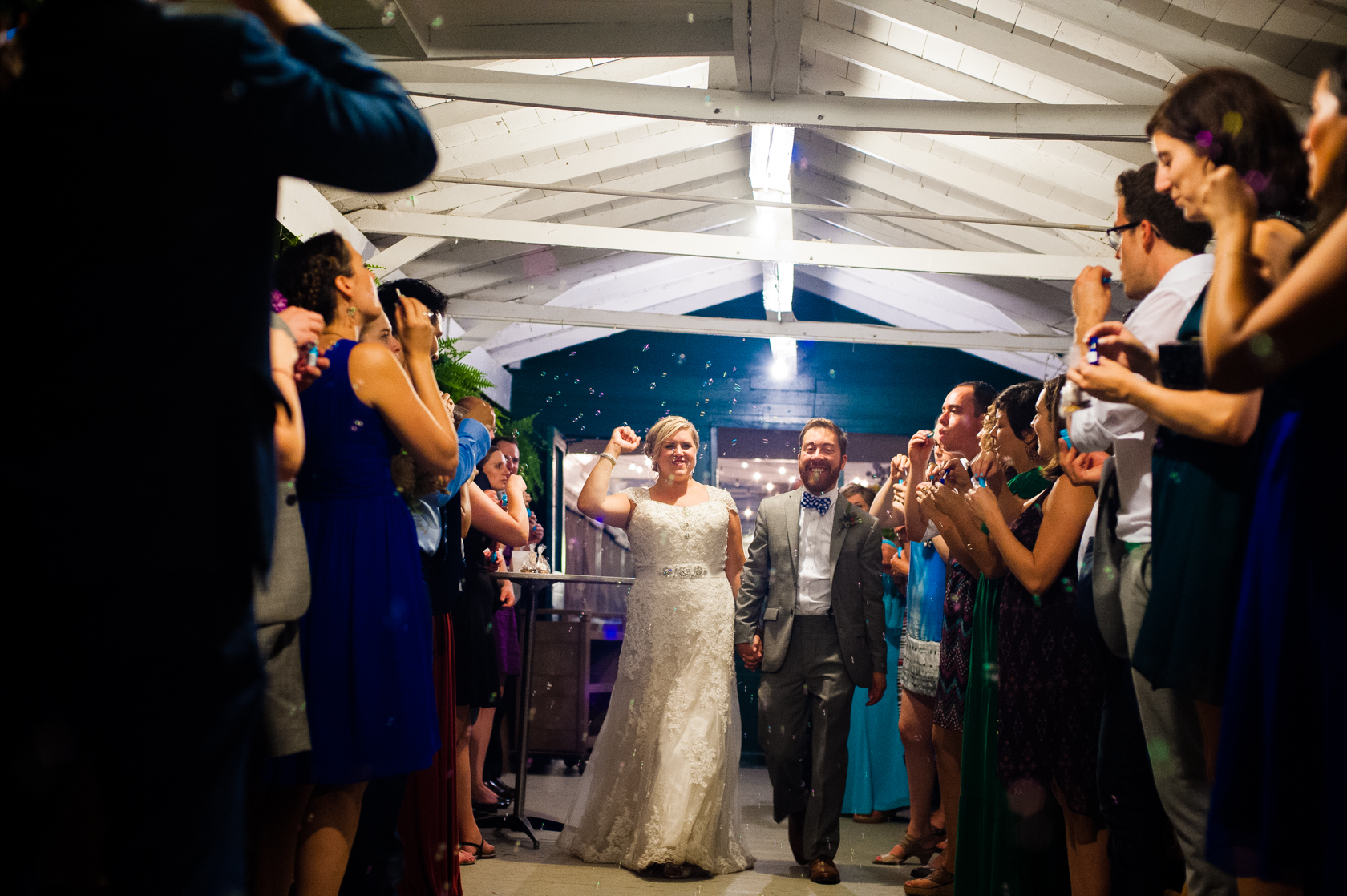 bride and groom run out of a summer camp mess hall with bubbles surrounding them
