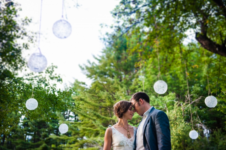 Beautiful couple embrace under diy hanging globes in a forest