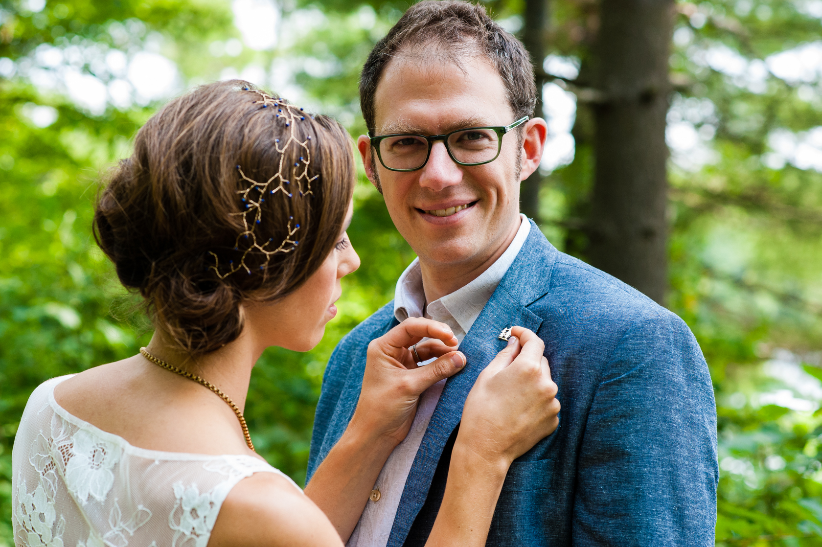 bride pins a lapel she made on her handsome groom