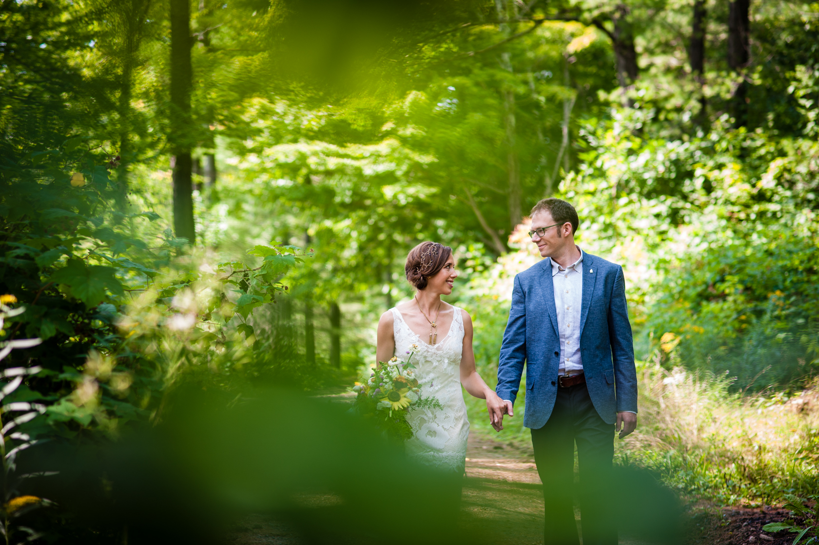 beautiful bride and groom hold hands and walk down a wooded path during their summer camp wedding
