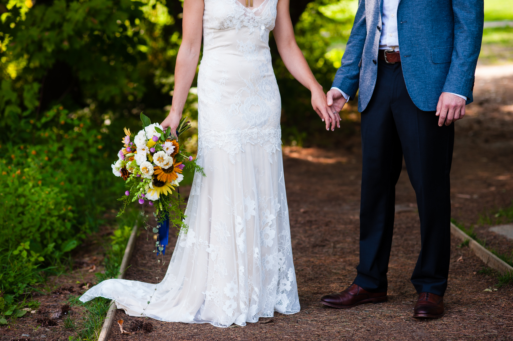 bride in gorgeous lace dress and groom in grey suit hold hands