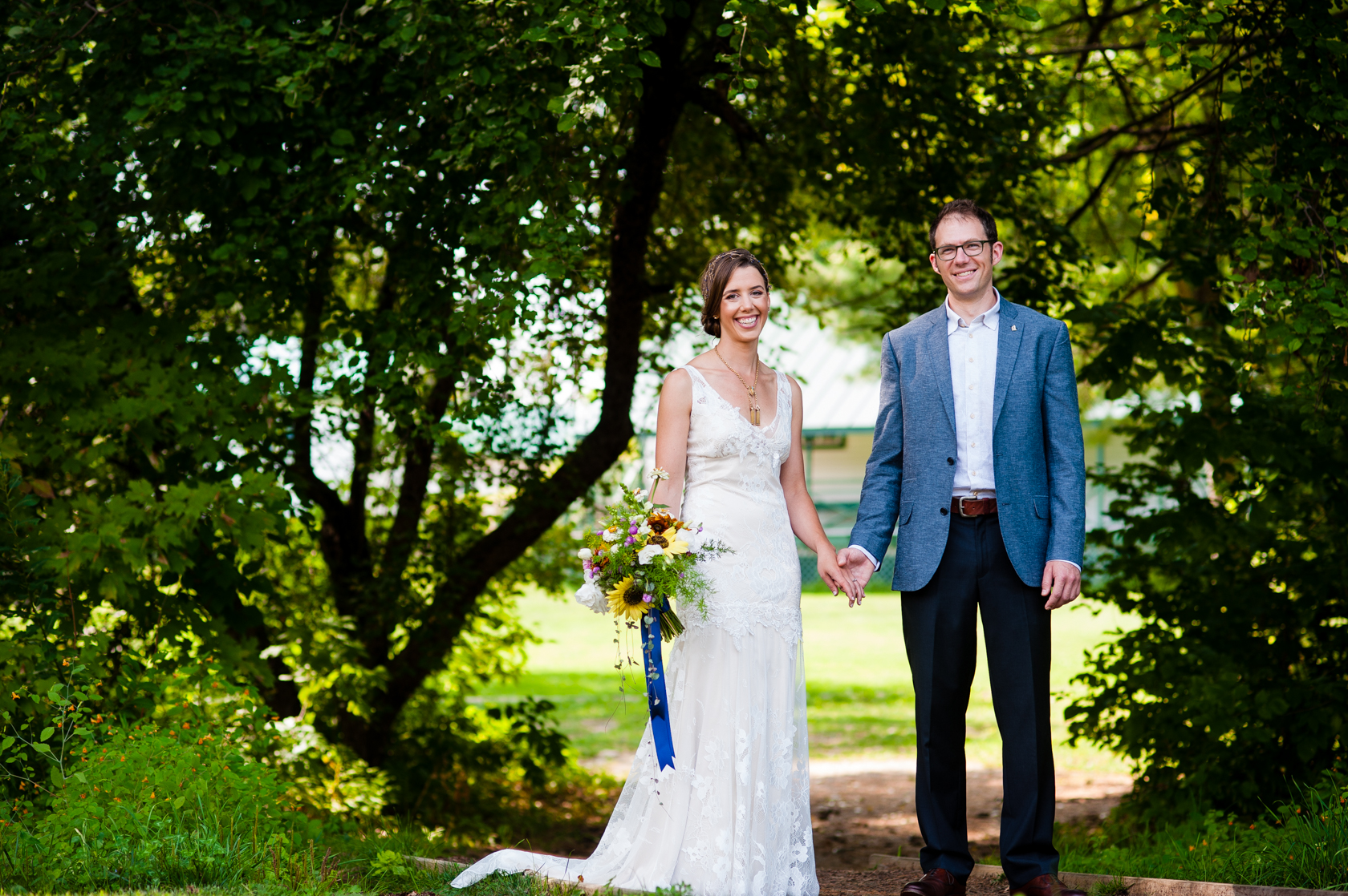 happy bride and groom holding hands in front of beautiful apple trees