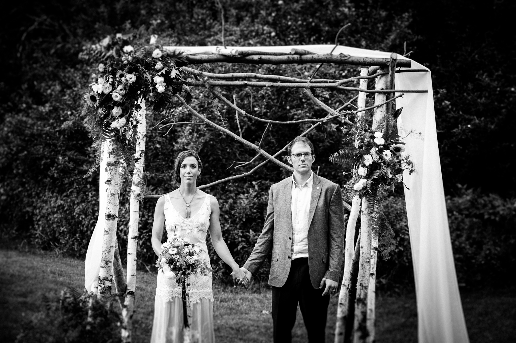 bride and groom hold hands in front their gorgeous handmade birch arbor
