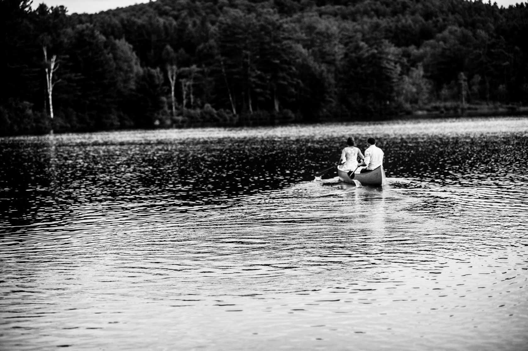 adventurous bride and groom paddle a canoe out on the lake during their summer camp wedding
