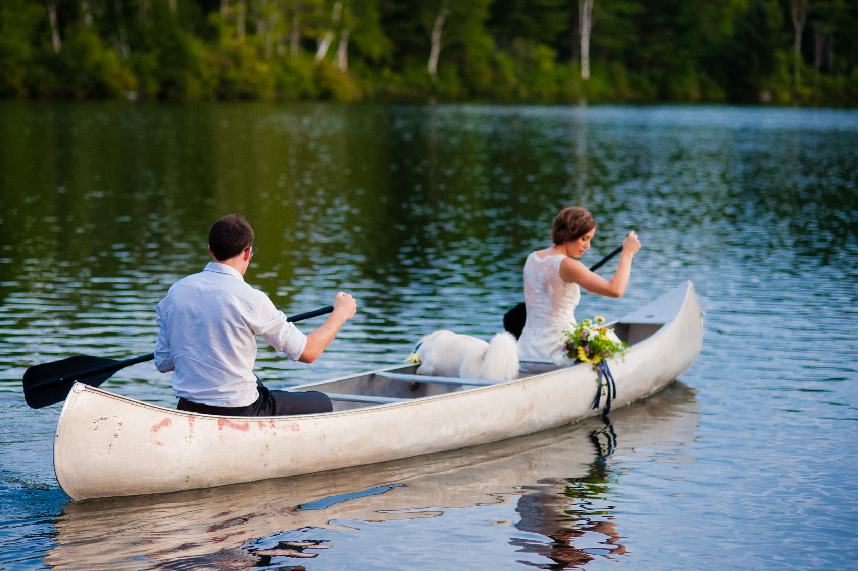 fun adventurous couple paddle a canoe on their wedding day with their dog