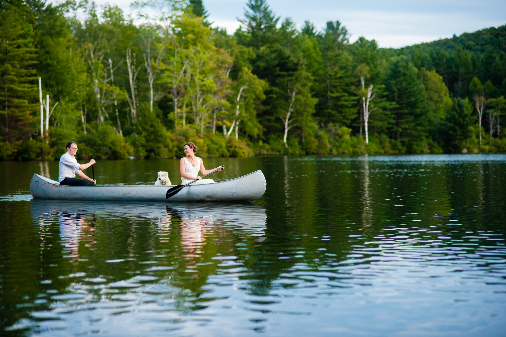 bride and groom adventure out on the lake in a canoe