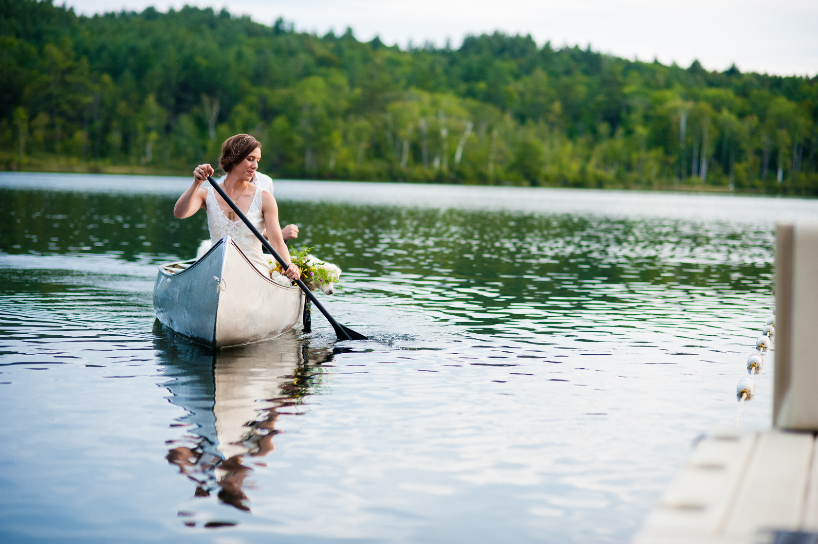 beautiful bride paddling a canoe on her wedding day