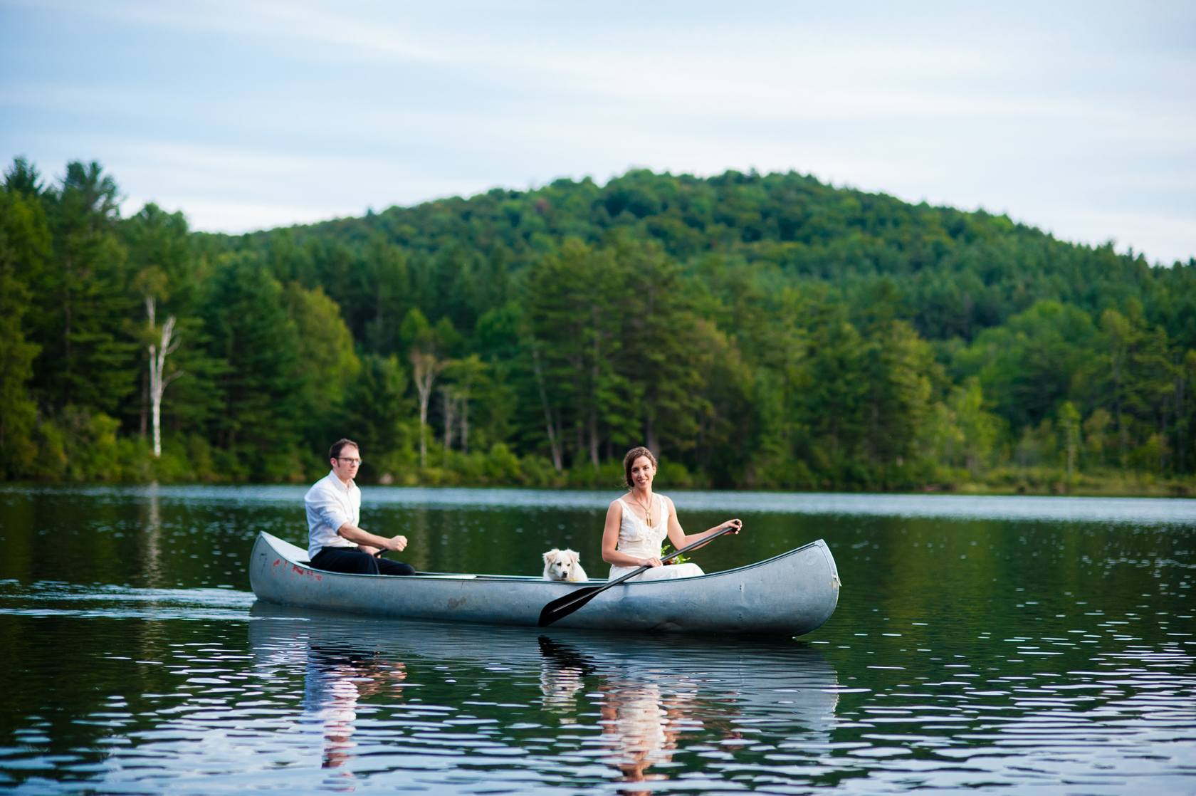 bride and groom having a blast paddling a canoe during their outdoor summer camp wedding