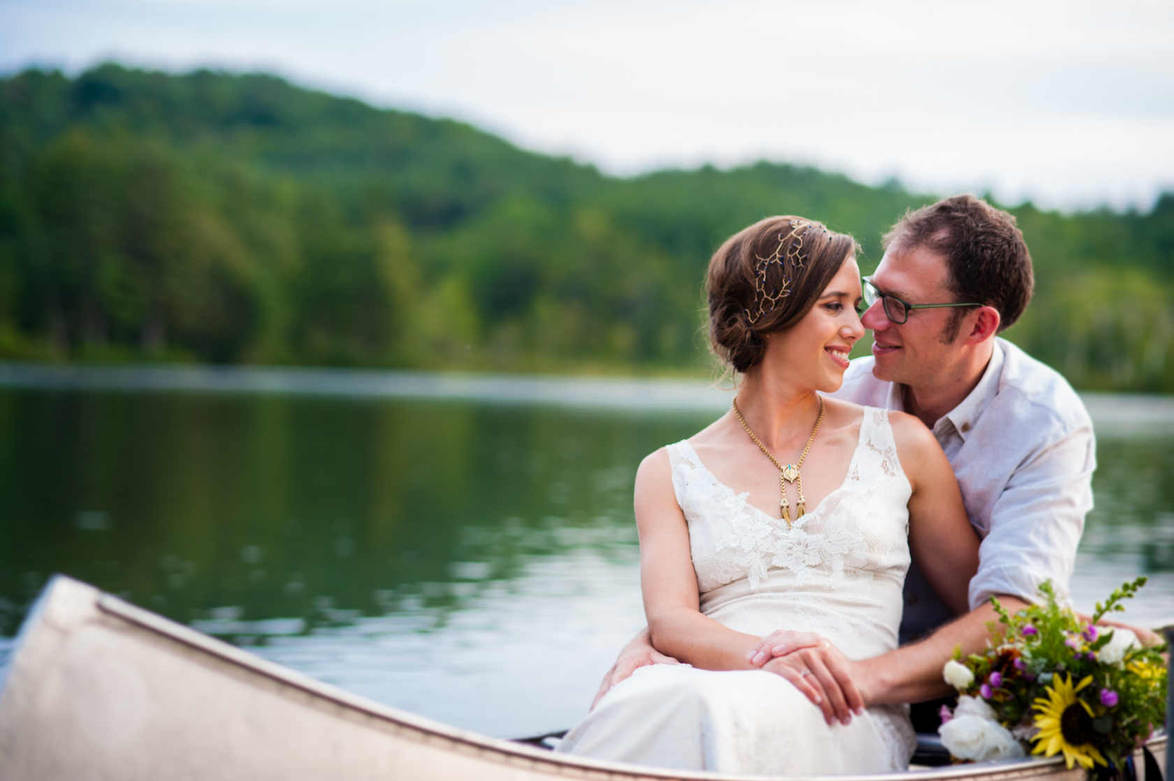 newly married couple snuggles up together in a canoe on their wedding day