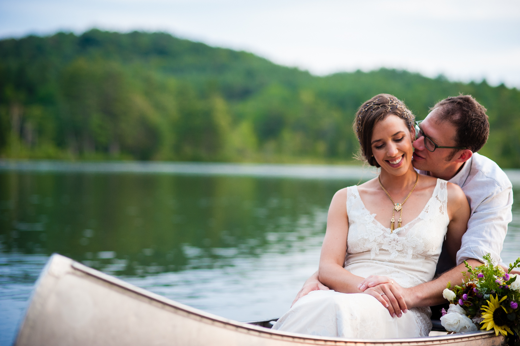groom gives his bride a kiss on the cheek during their post wedding canoe paddle on the lake