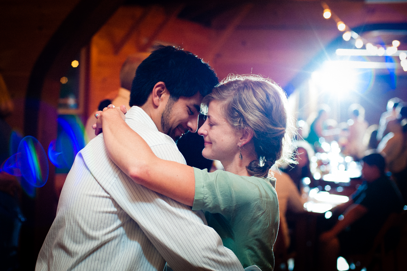 a young couple dancing during a summer camp wedding reception