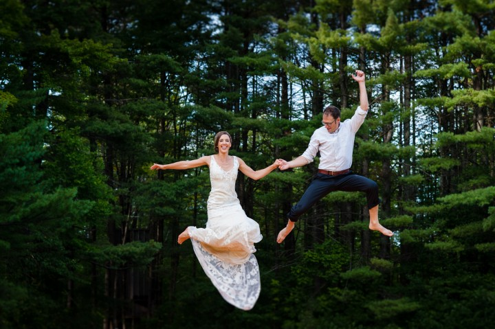 adventurous bride and groom jumping in the air on a big trampoline  on their wedding day