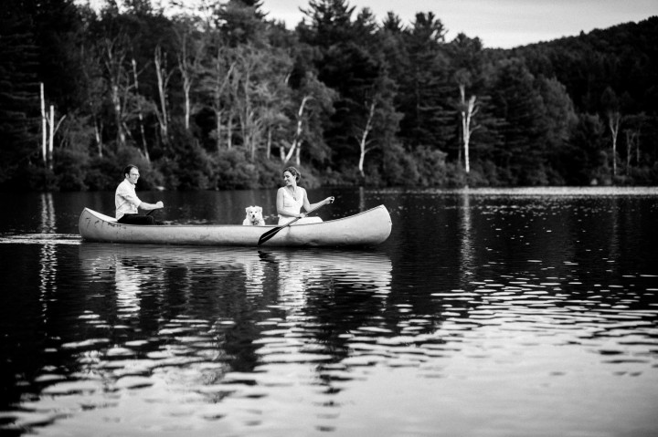 newly married couple paddles a canoe across the lake during their summer camp wedding