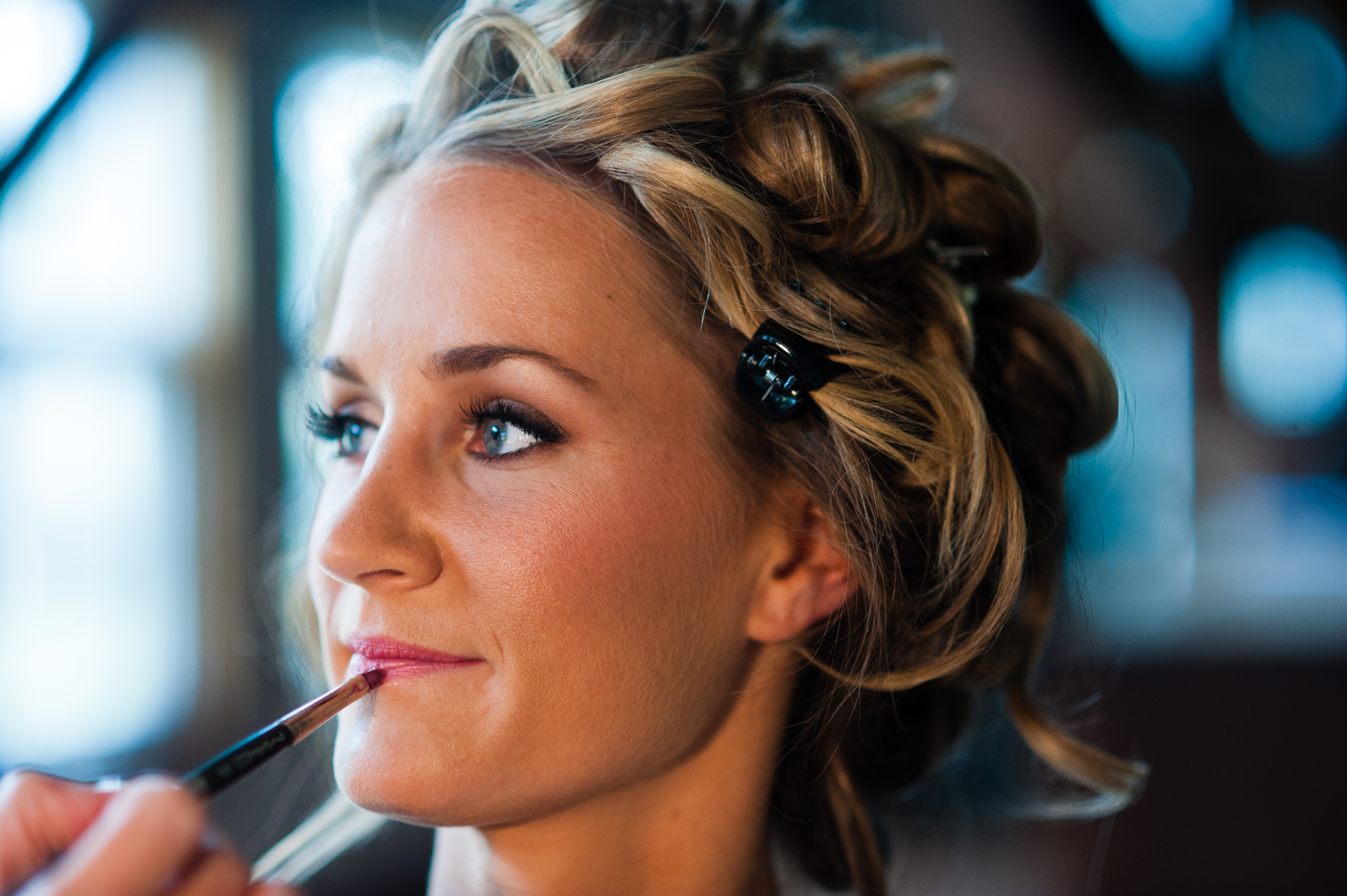 beautiful blonde bride getting her makeup done before her rustic farm wedding
