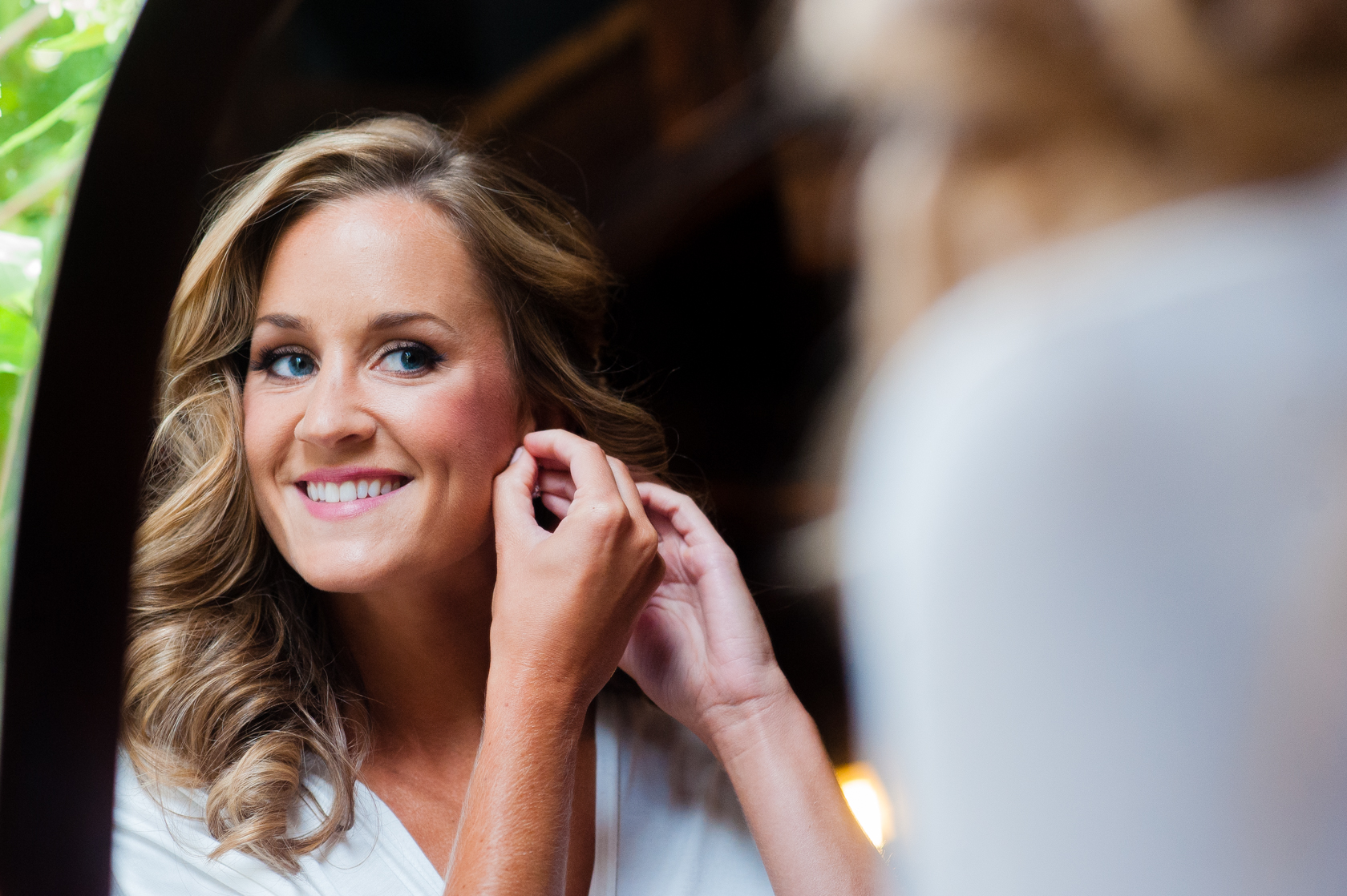 beautiful bride puts her earrings on in the mirror
