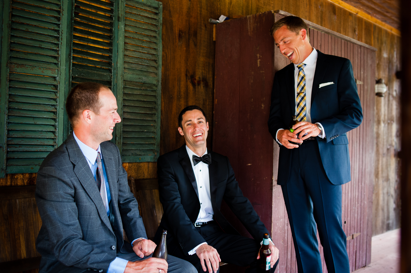 groom and his best men relax on their cabins front porch with a beer in hand