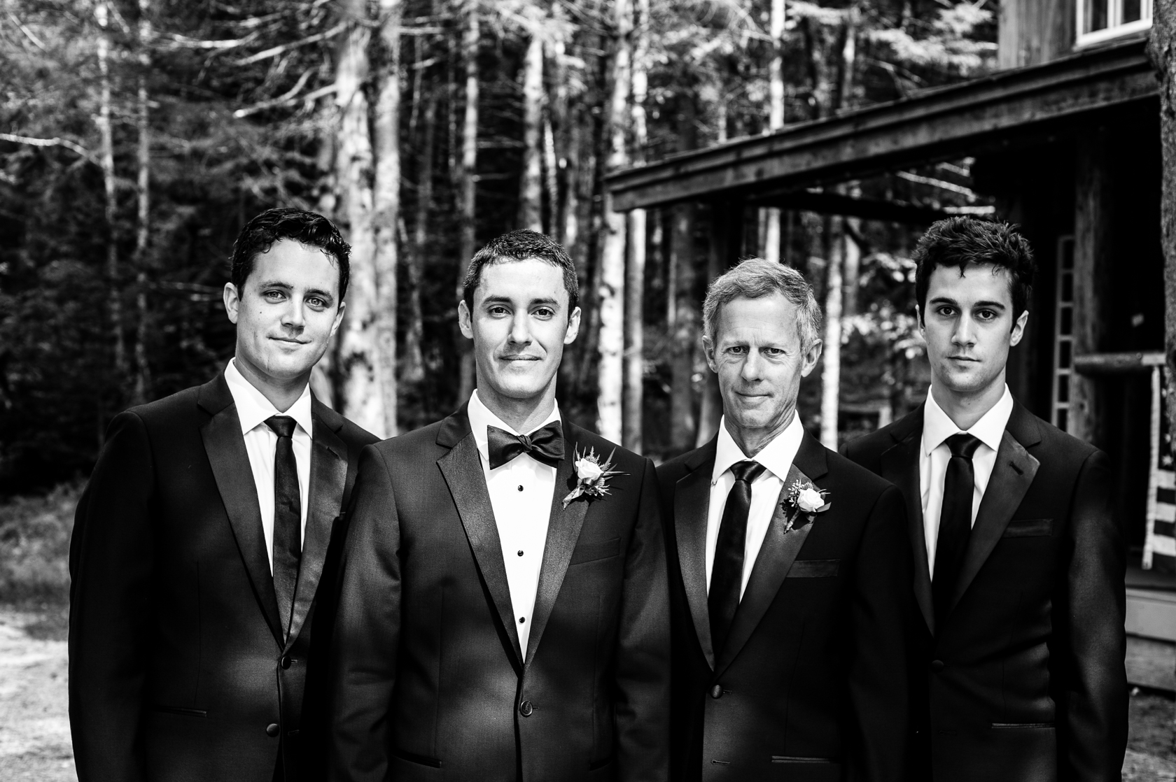 groom and his best men pose for a portrait in the woods