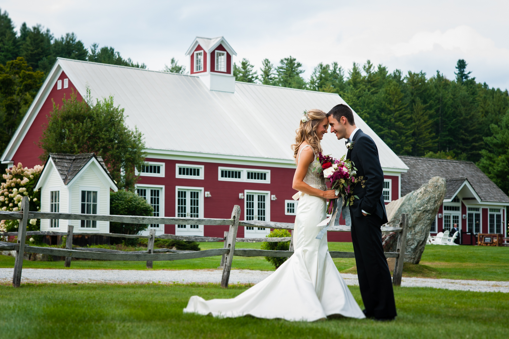 bride and groom forehead to forehead in front of red farm barn