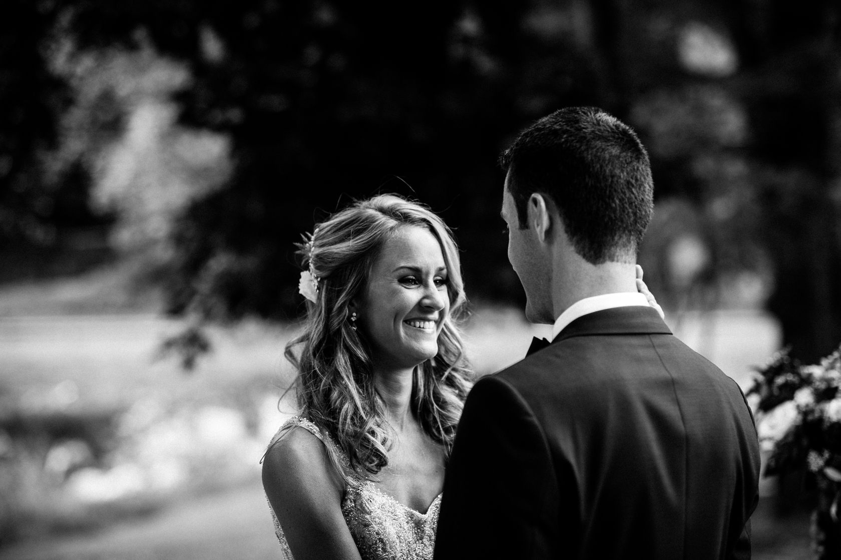 beautiful black and white image of bride smiling at her groom