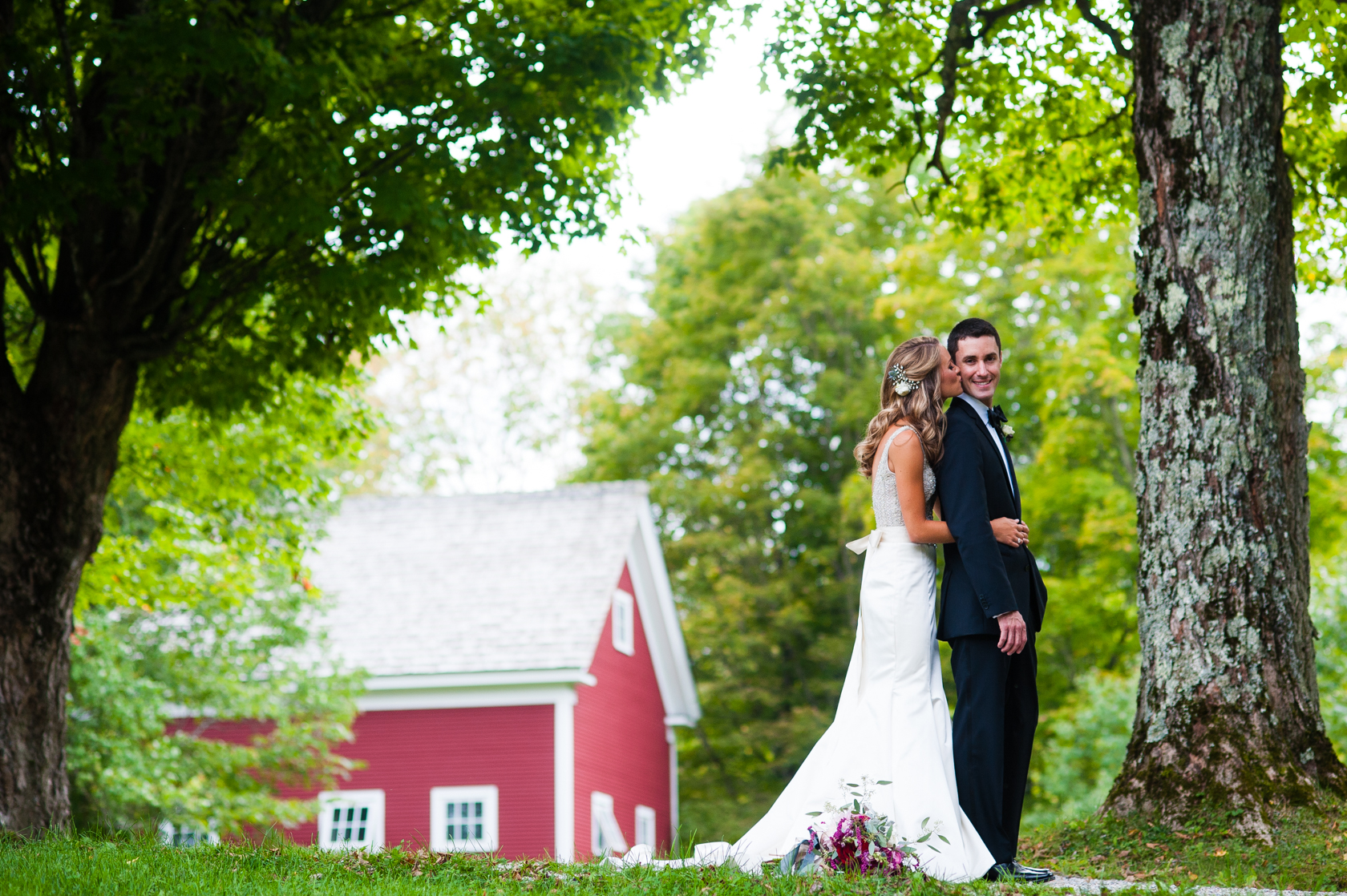 bride gives her new husband a kiss on the cheek during their gorgeous farm wedding