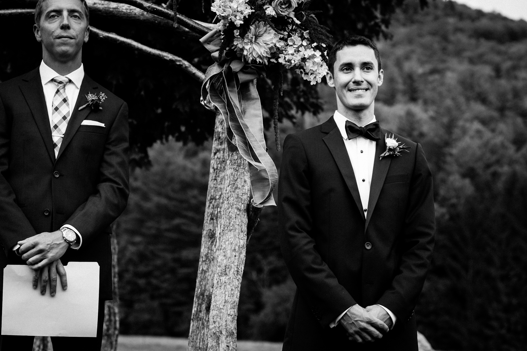 groom waits for his bride at the end of the ceremony aisle