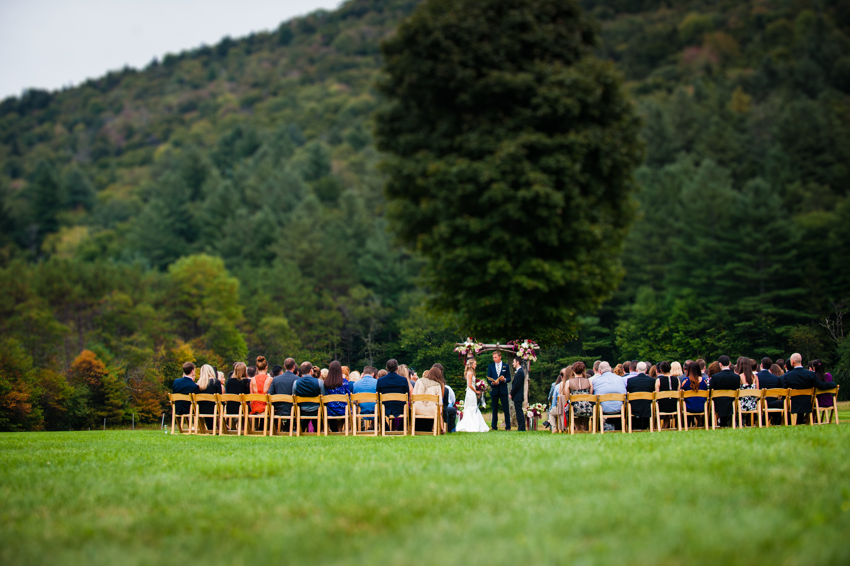 a wedding ceremony in a gorgeous field with vermonts green mountains  behind