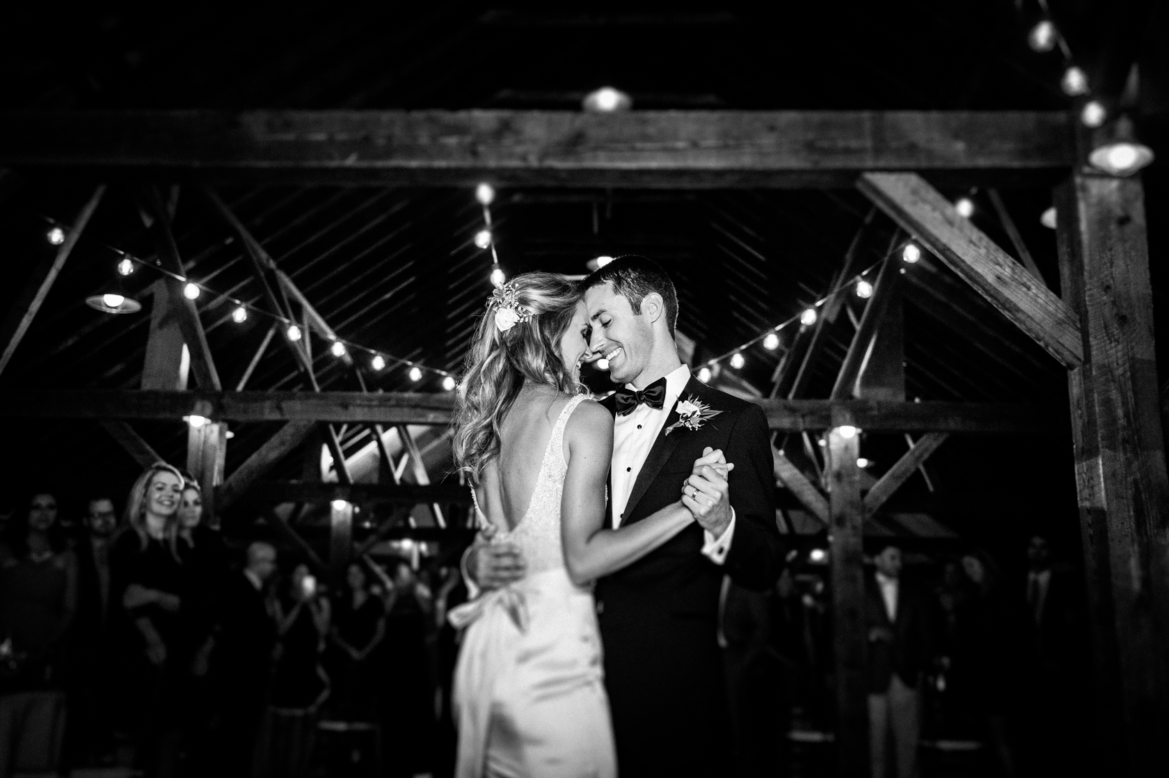 bride and groom perform their first dance underneath twinkling christmas lights