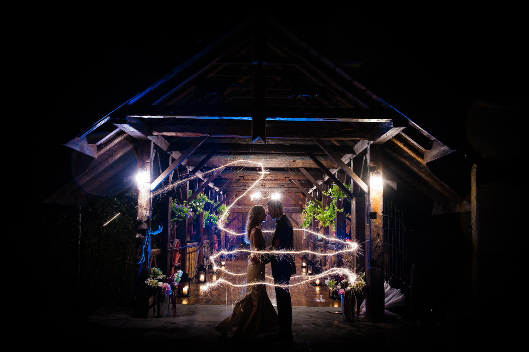 bride and groom stand in the center of a ring of sparklers in front of their gorgeous barn wedding venue