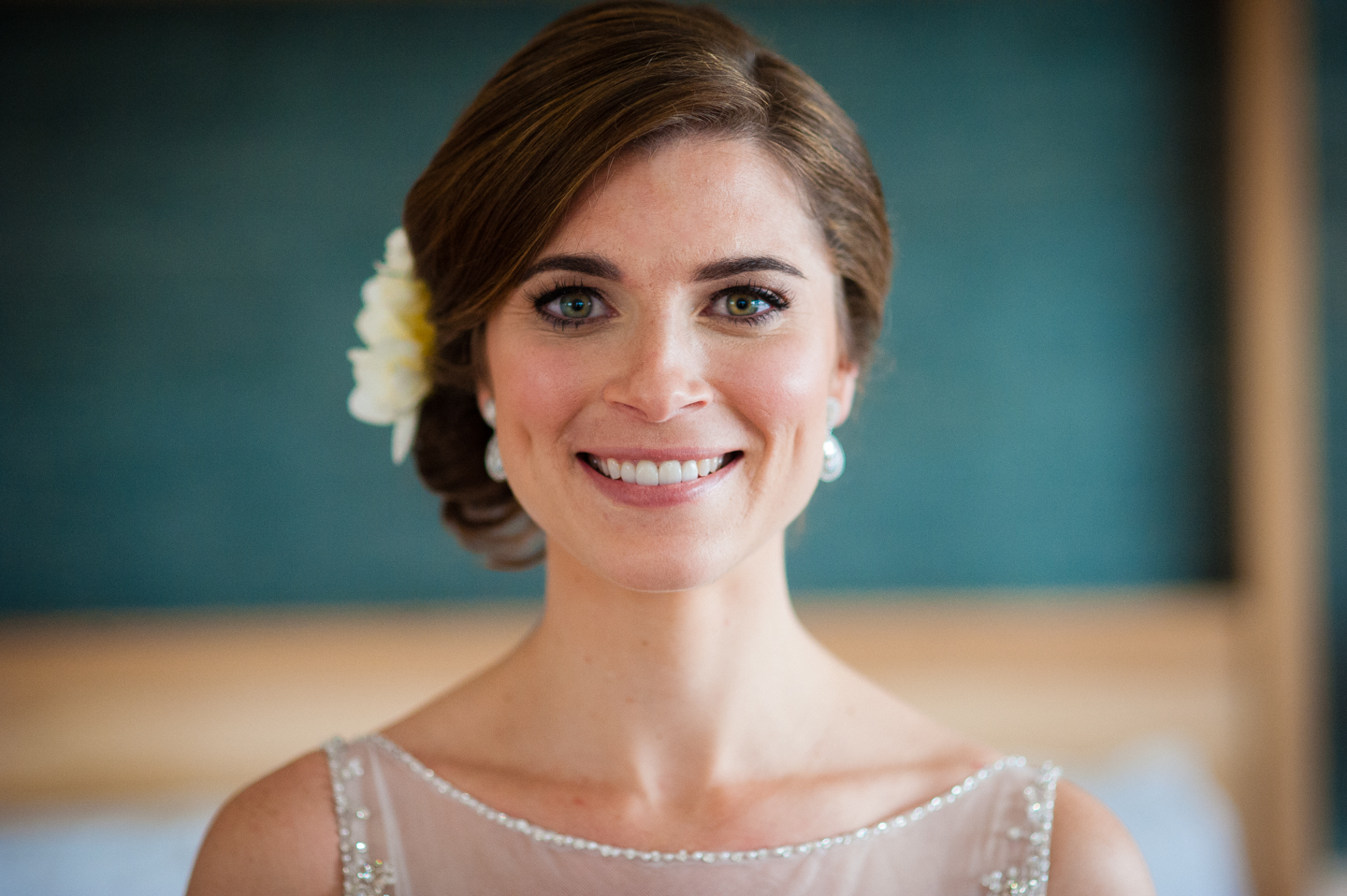 beautiful bride with a white flower in her hair smiling
