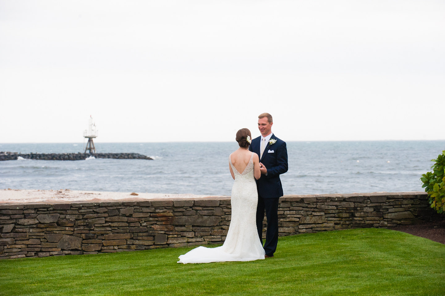bride and groom looking at each other by the ocean