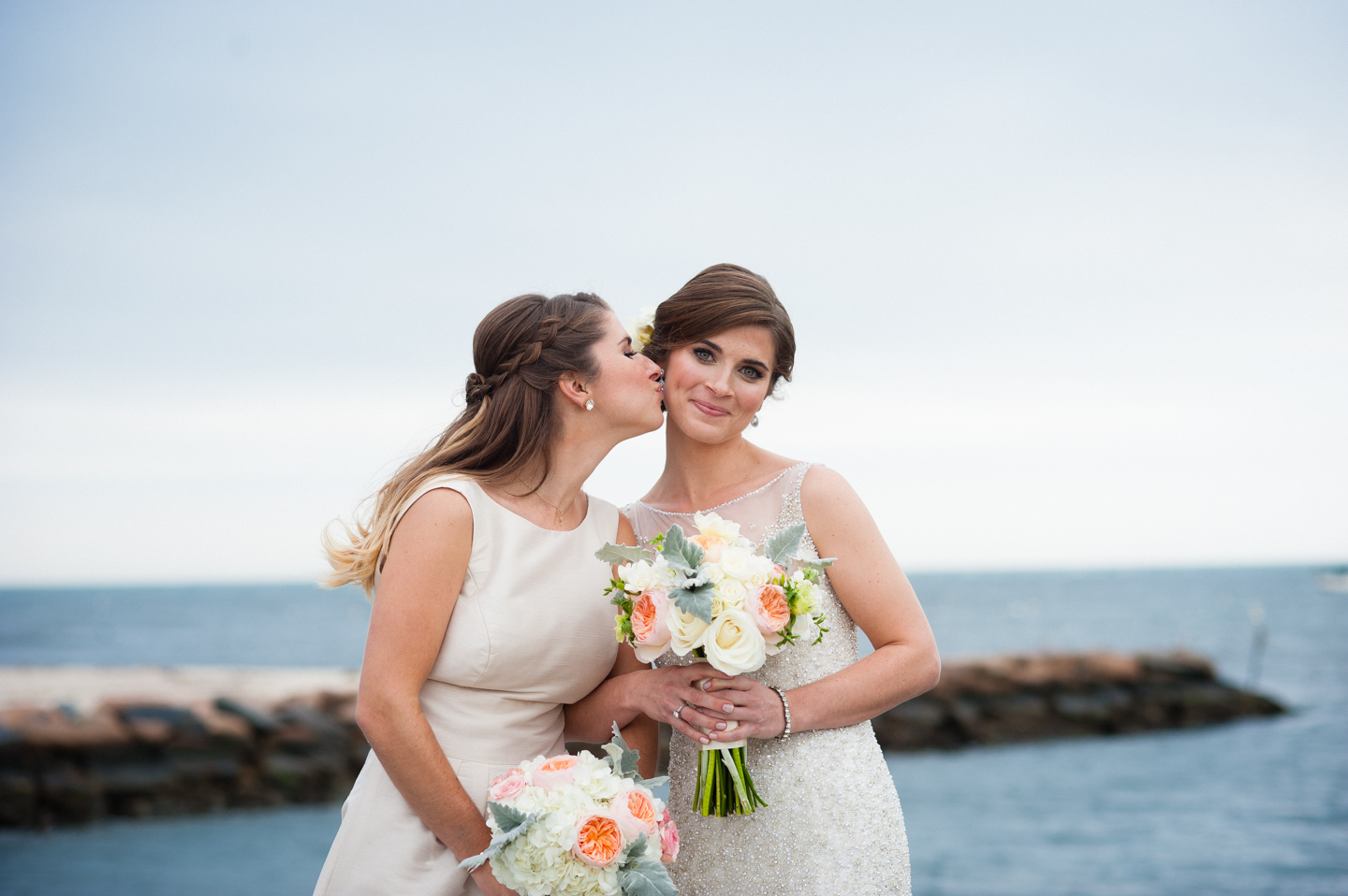bridesmaid gives the beautiful bride a kiss on the cheek