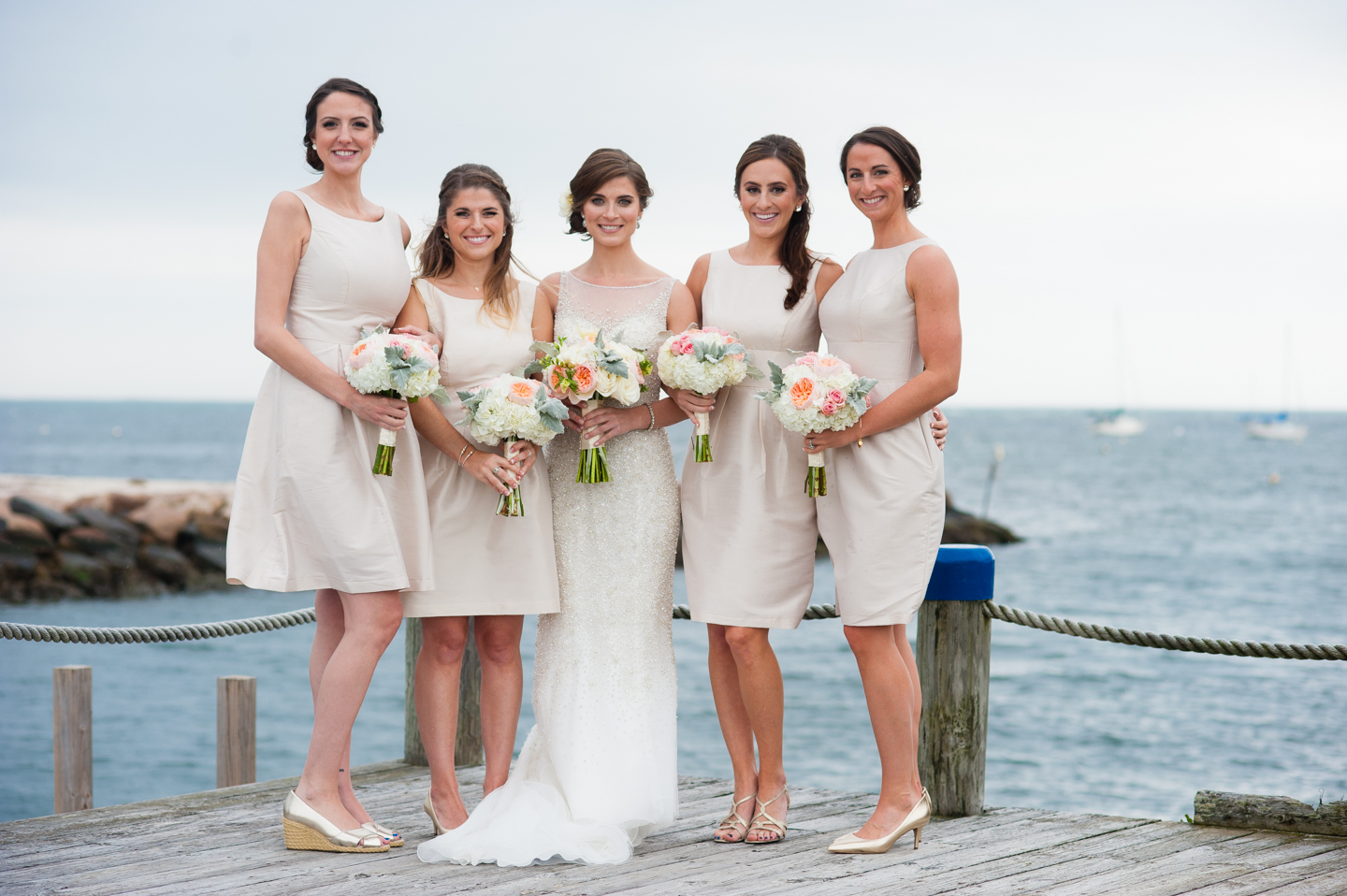 beautiful bridesmaids in classic cream dresses stand by the ocean