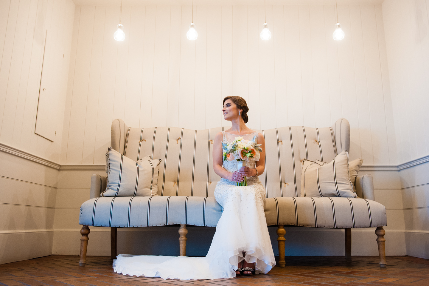 beautiful bride poses on the couch for a bridal portrait