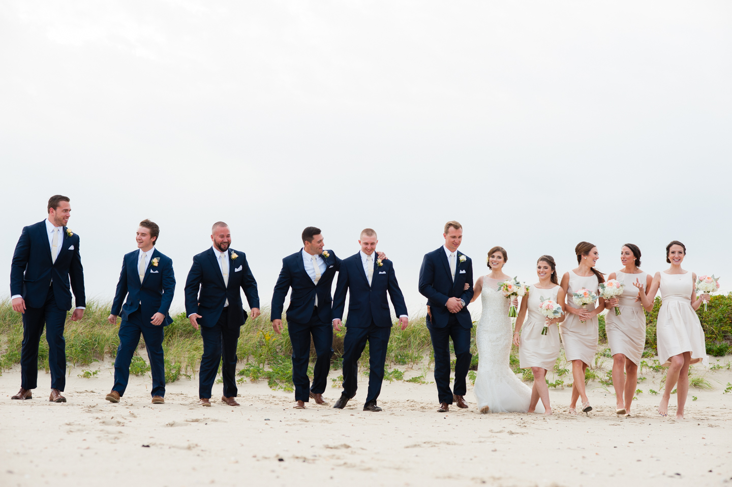 fun wedding party walks through the sand on the beach laughing