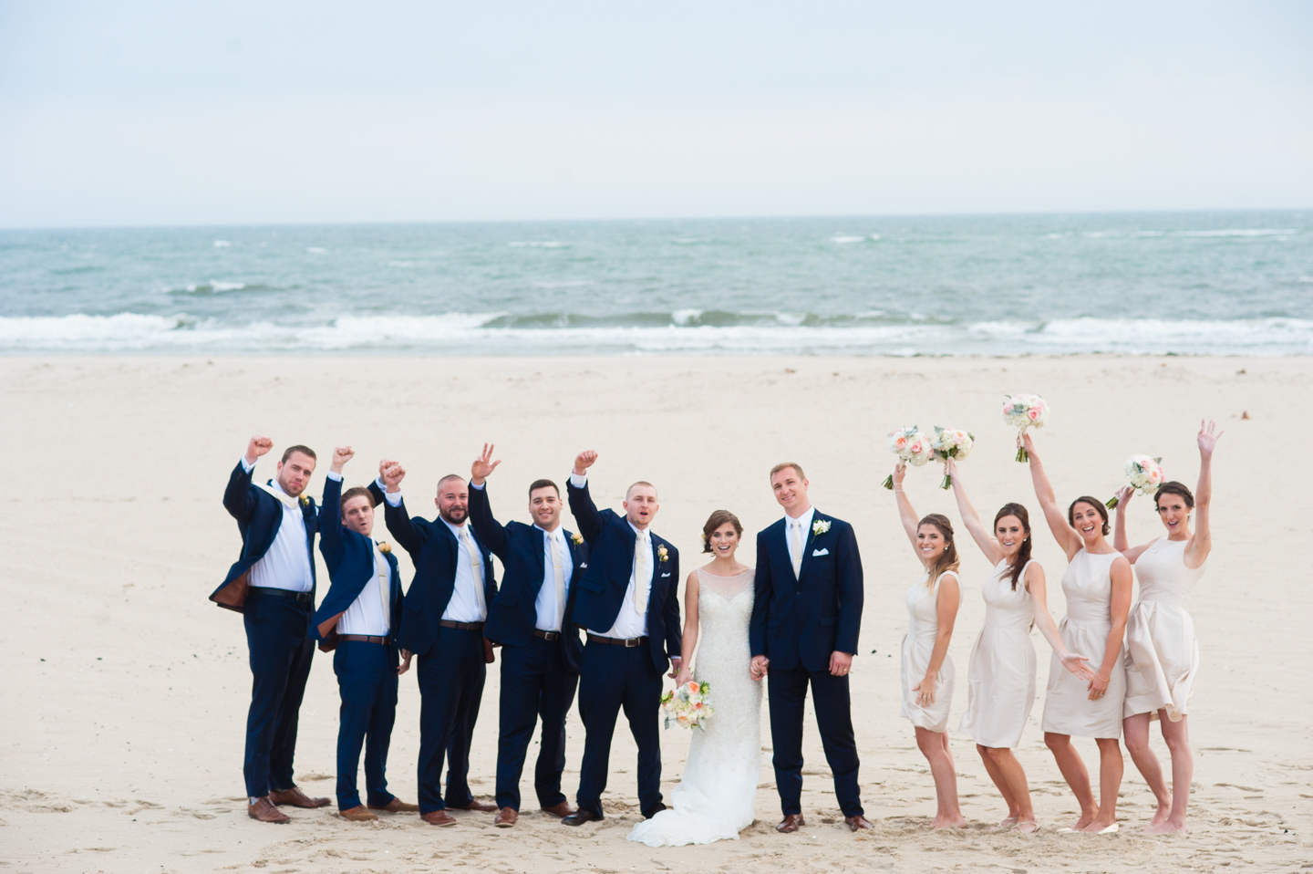 bride and groom cheer with their wedding party with the ocean behind