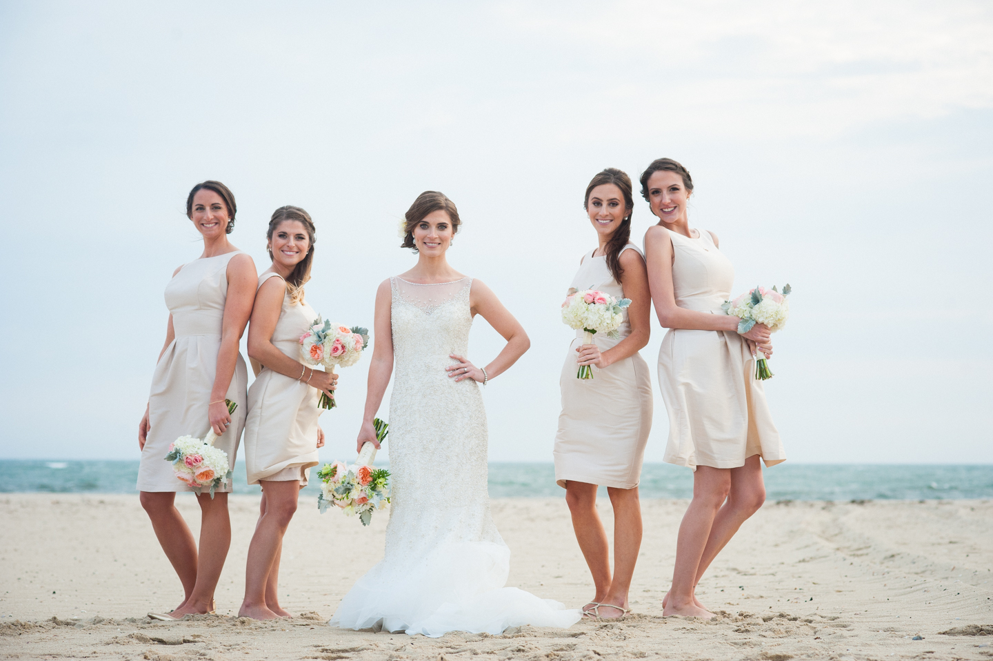 bride and her bridesmaids stand by the ocean in gorgeous white and cream dresses