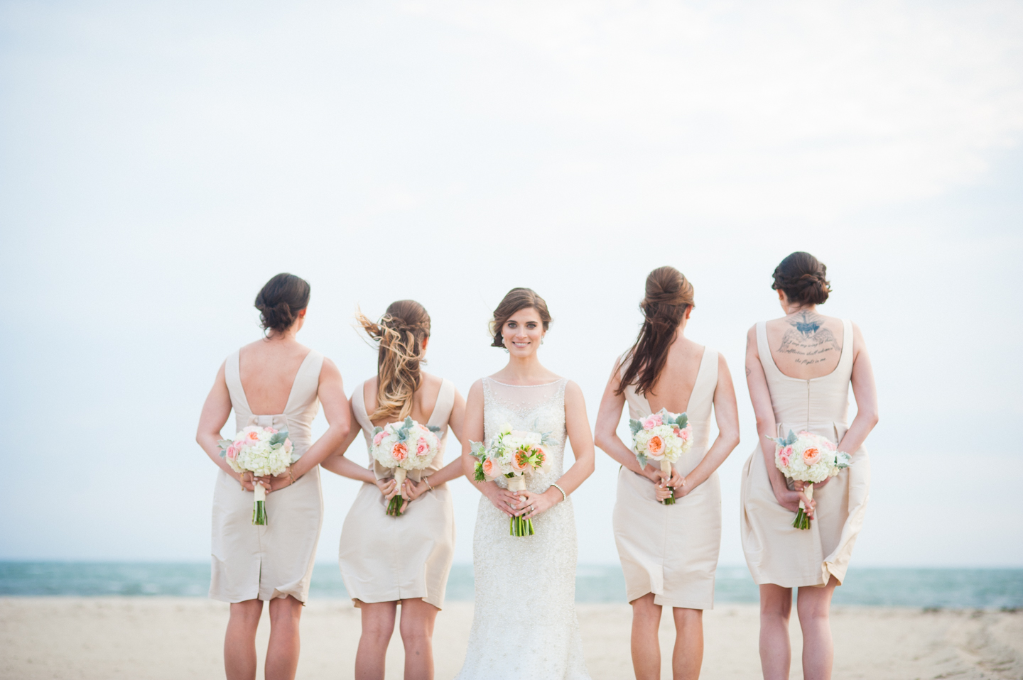 beautiful bride faces camera while her bridesmaids show off their flowers and the backs of their dresses