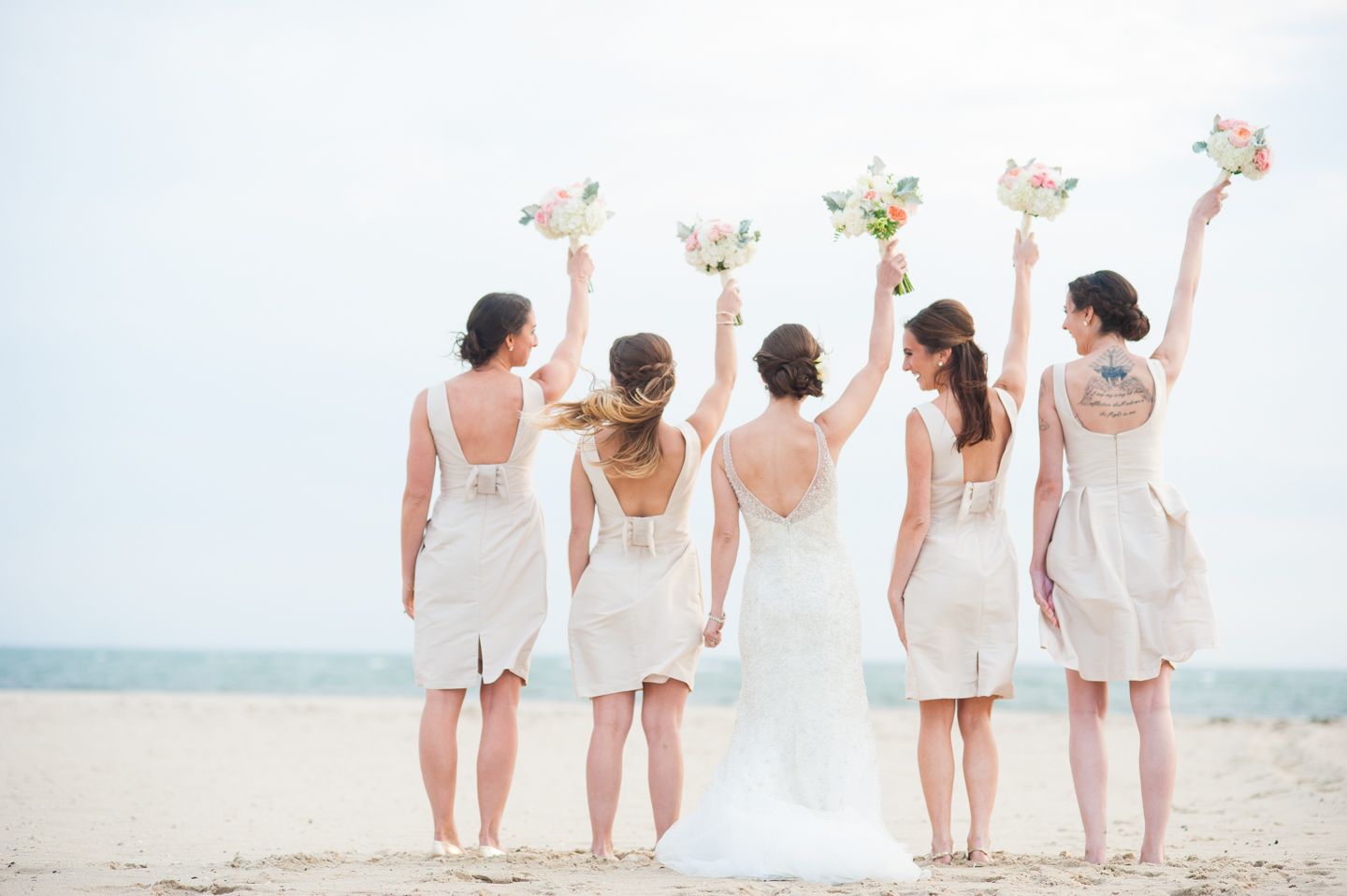 the ladies cheer and laugh at each other during wedding party pictures on the beach