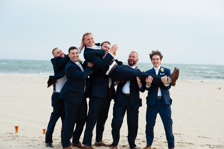 the groomsmen hoist the groom up on their shoulders by the ocean
