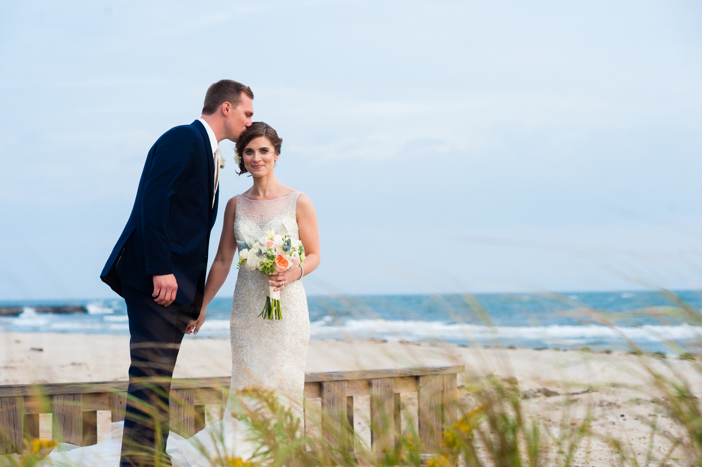 groom gives his gorgeous bride a kiss on the head in the dune grass by the beach