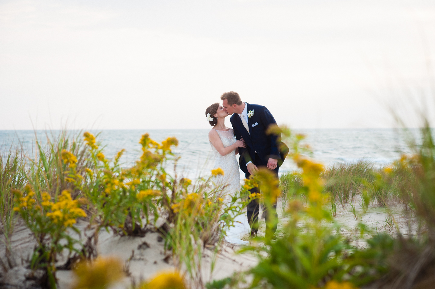 newly married couple kisses by the ocean with yellow flowers all around