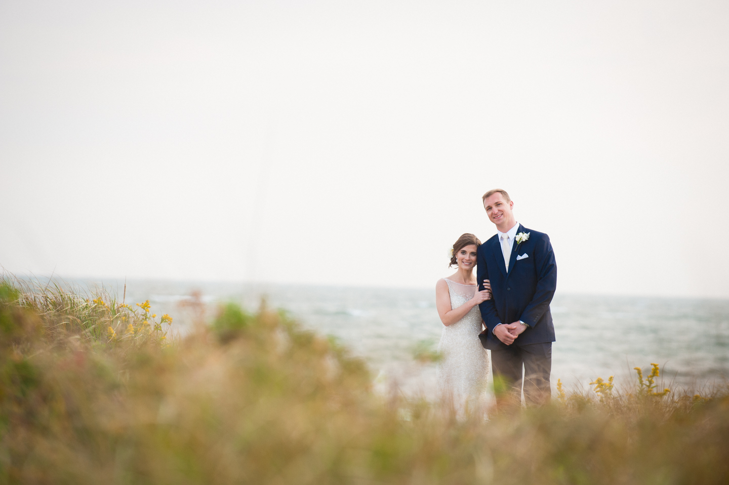bride and groom stand side by side with sea grass and ocean all around