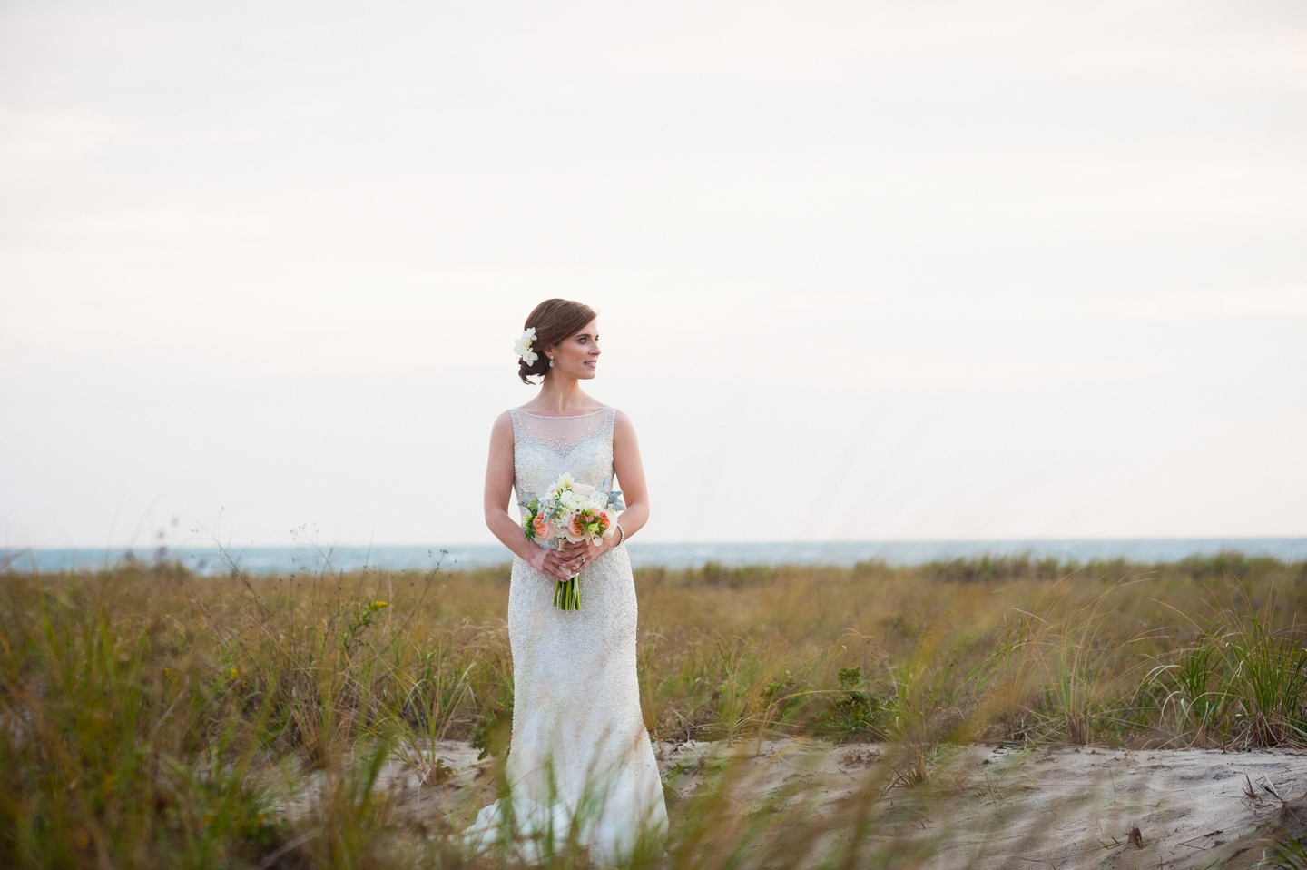 bride looks off in to the distance with the sea grass and ocean all around