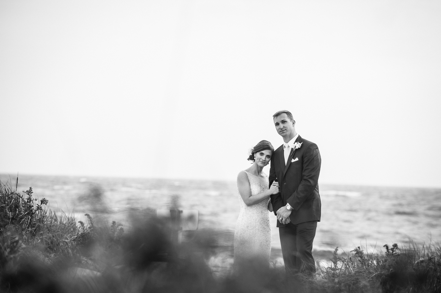 bride rests her head on her husbands shoulder with stormy sea behind them