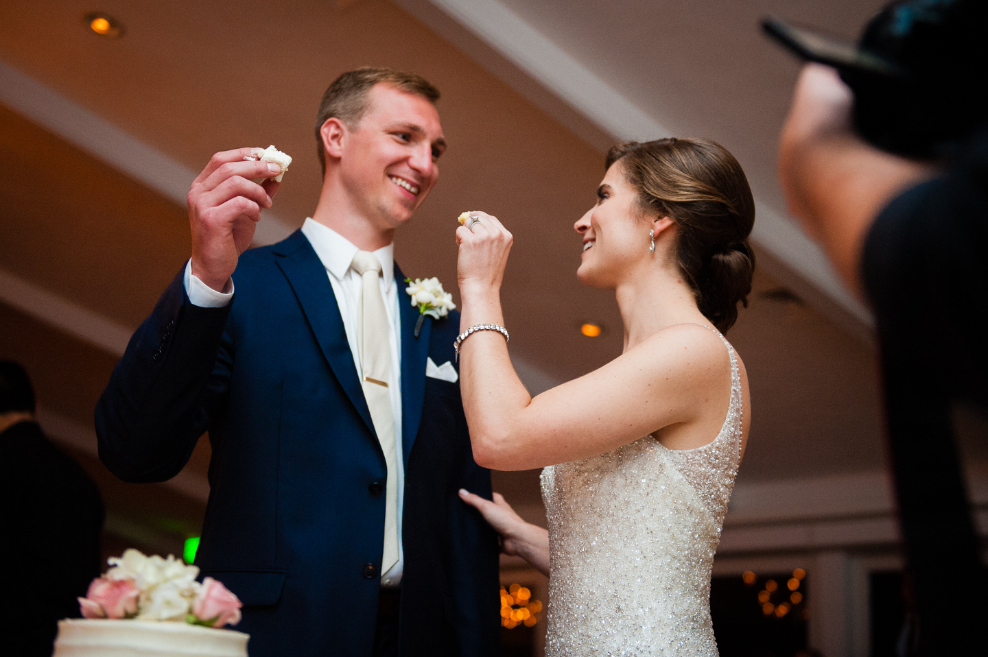 bride and groom laughing as they feed each other wedding cake