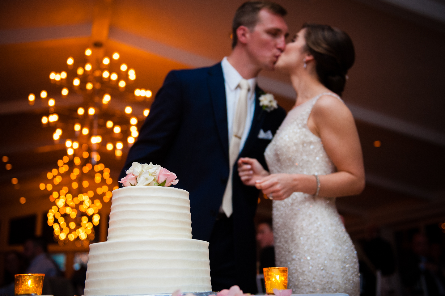 newly married couple kisses behind their classic white wedding cake