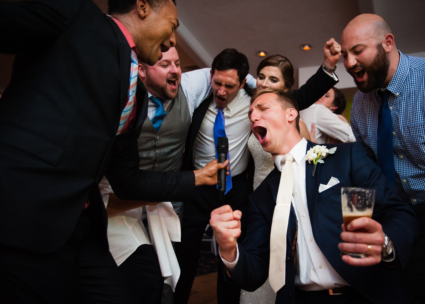 groom sings on the dance floor with the band