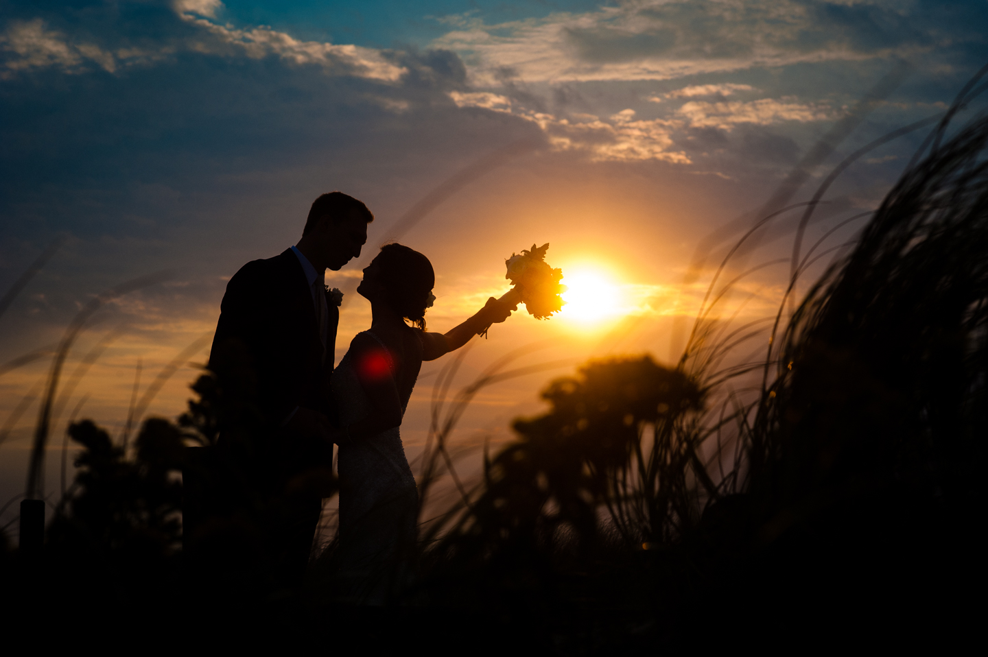 bride raises her bouquet with a gorgeous fall beach sunset silhouetting them
