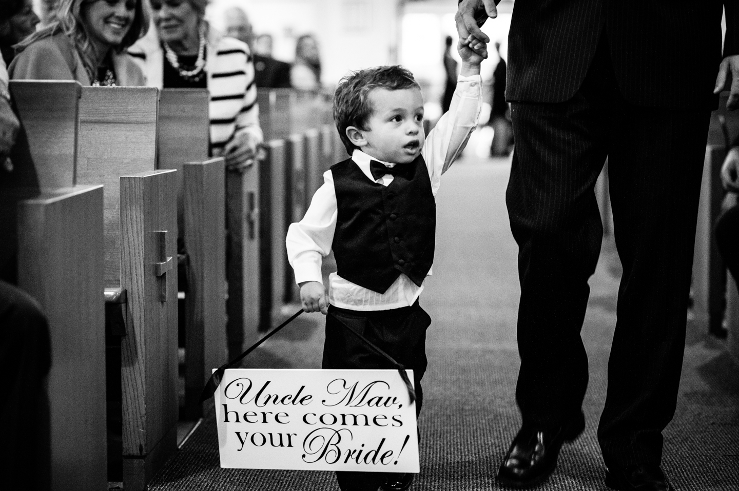 adorable ring bearer holds a here comes the bride sign